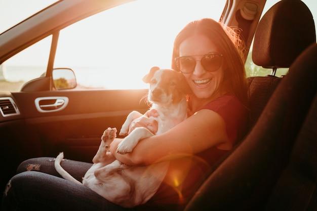 Junge frau und ihr süßer hund in einem auto bei sonnenuntergang. reisekonzept