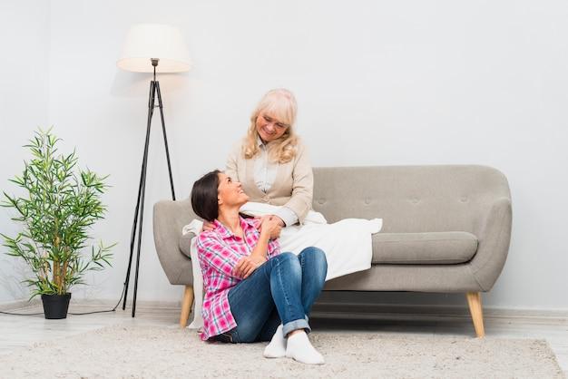 Junge frau und ihre ältere mutter, die einander sitzen im wohnzimmer betrachtet