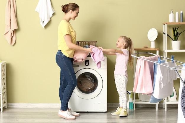 Junge frau und ihre kleine tochter, die zu hause wäsche waschen