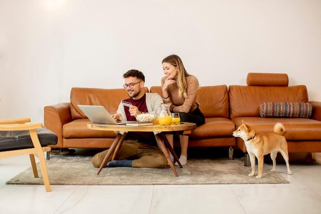 Junge frau und junger mann, die laptop für online-zahlung verwenden, während sie mit ihrem shiba inu-hund zu hause am sofa sitzen