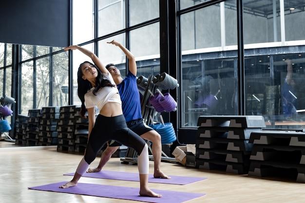 Junge frau und junger mann stehen yoga auf der yogamatte im fitnessraum mit kopienraum. junge paare mit übung, indem sie zusammen yoga im innenbereich machen. konzept der übung mit yoga.