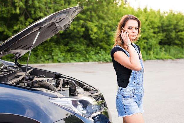 Junge frau und kaputtes auto, die am handy um hilfe rufen.