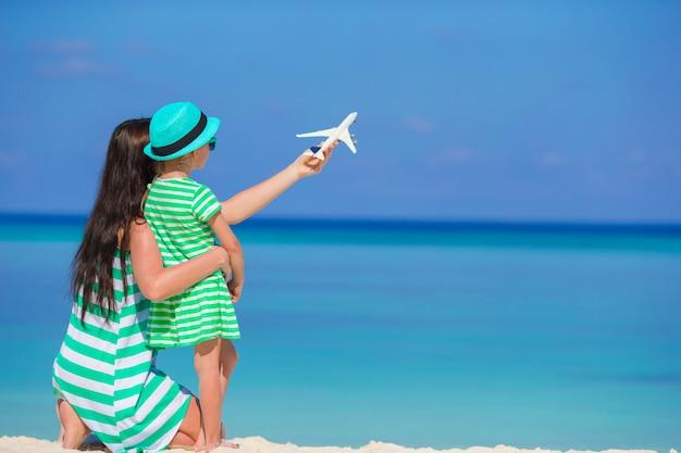 Junge frau und kleines mädchen mit miniatur des flugzeuges am strand