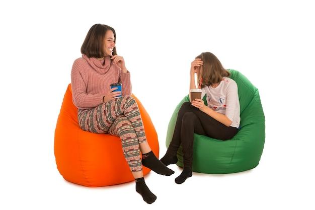Junge frau und lachendes mädchen sitzen auf sitzsäcken und trinken kaffee lokalisiert auf weiß