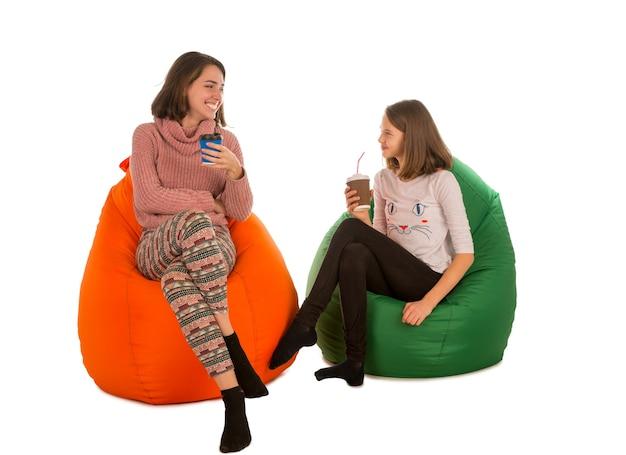 Junge frau und lächelndes mädchen sitzen auf sitzsackstühlen und trinken kaffee lokalisiert auf weiß