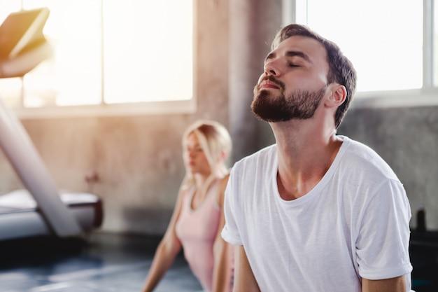 Junge frau und männer, die gesundes körpertraining des lebensstils in der turnhalle ausbilden