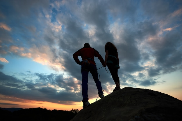 Junge frau und mann, die auf dem felsen stehen und auf laufende wolken achten.