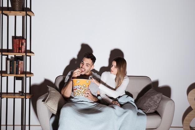 Junge frau und mann, die fernsehen und popcorn auf sofa essen