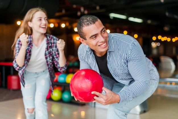 Junge frau und mann, die in einem bowlingspielverein steht