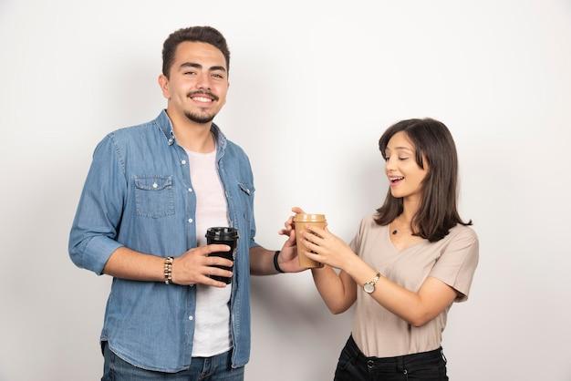 Junge frau und mann, die kaffee auf weiß teilen.
