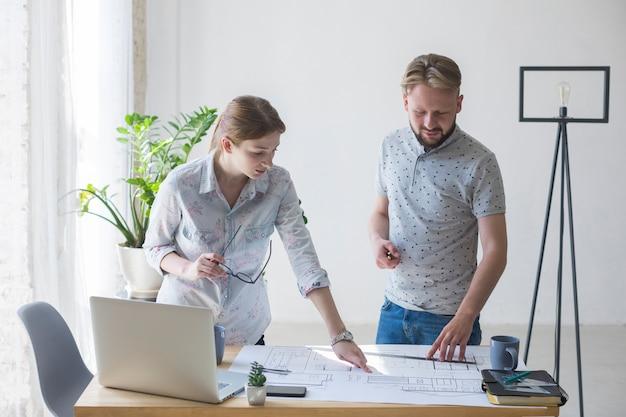 Junge frau und mann, die zusammen an plan im büro arbeitet