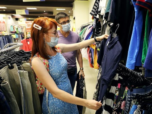 Junge frau und mann im bekleidungsgeschäft, die neue kleidung in der verkaufsabteilung auswählen
