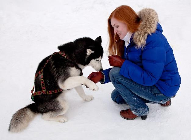 Junge frau und schlittenhund im winter
