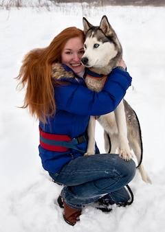 Junge frau und siberian husky im winter
