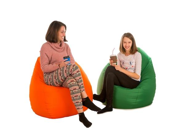 Junge frau und süßes mädchen sitzen auf sitzsackstühlen und trinken kaffee lokalisiert auf weiß