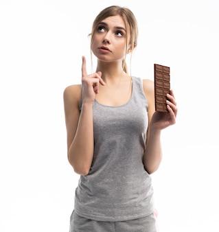 Junge frau unglücklich mit ihrem gewicht, das schokolade hält, lokalisiert auf weiß.