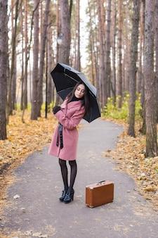 Junge frau unter regenschirm im herbstpark