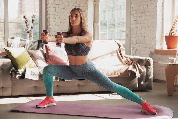 Junge frau unterrichtet zu hause online-kurse für fitness, aerobic, sportlichen lebensstil während der quarantäne. aktiv werden, während isoliert, wellness, bewegungskonzept. übungen mit gewichten, gleichgewicht.