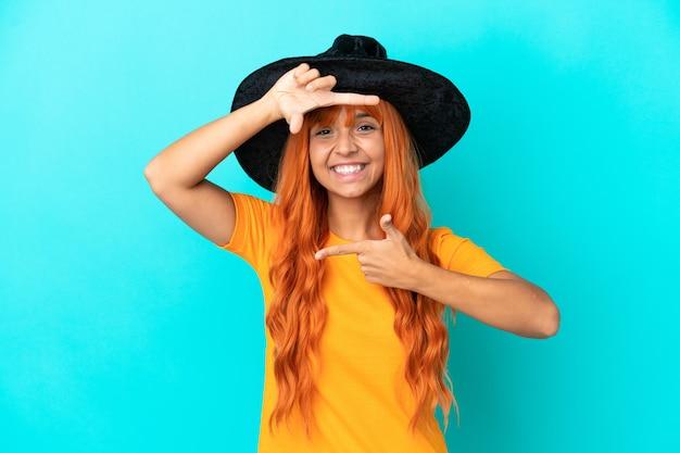 Junge frau verkleidet als hexe auf blauem hintergrund fokussierung gesicht isoliert. rahmensymbol