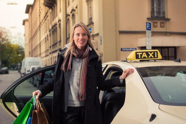 Junge frau verlässt ein taxi mit einkaufstüten