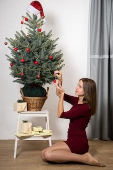 Junge frau verstaut geschenke unter dem weihnachtsbaum