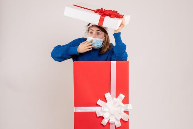Junge frau versteckt sich in geschenkbox auf weiß