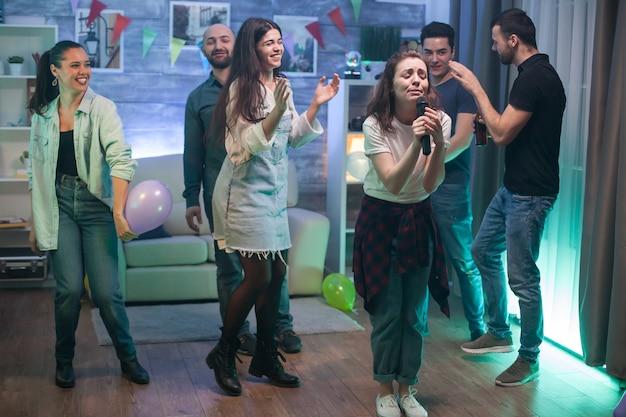 Junge frau voller emotionen auf der party ihrer freunde, die karaoke macht.