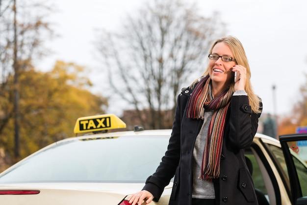 Junge frau vor taxi mit telefon