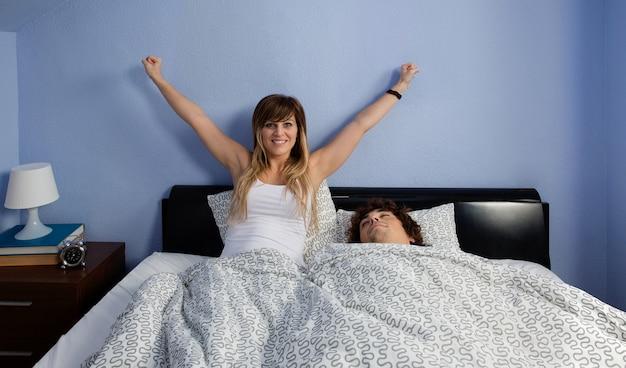 Junge frau wacht im bett auf, während ihr mann schläft