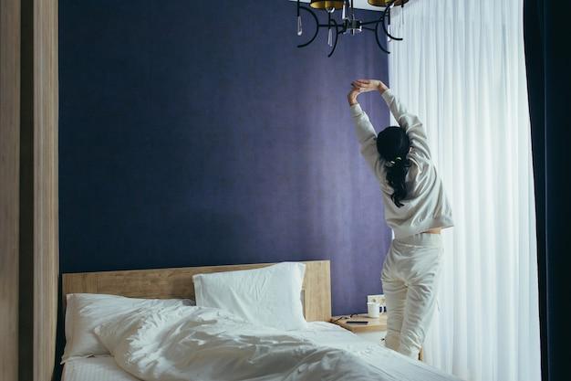 Junge frau wachte am morgen im schlafzimmer auf