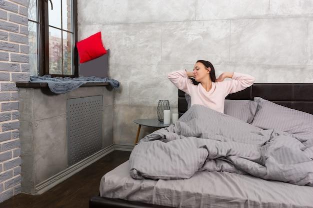 Junge frau wachte auf und streckte sich, während sie im bett saß und einen schlafanzug im schlafzimmer im loft-stil mit grauen farben trug