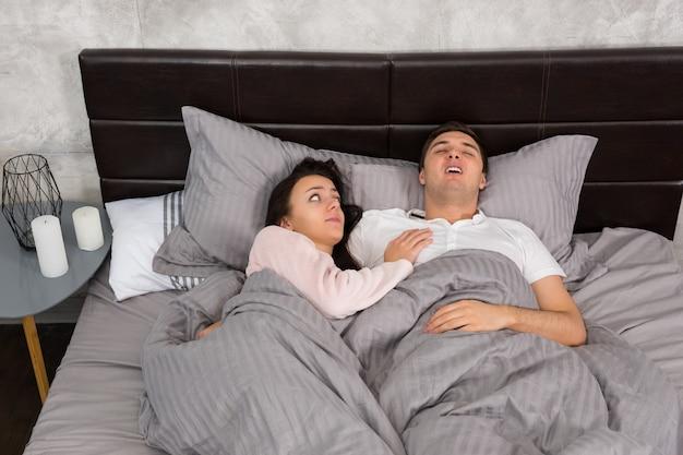 Junge frau wachte auf, weil ihr freund beim schlafen im bett schnarchte und im schlafzimmer einen schlafanzug im loft-stil mit grauen farben trug