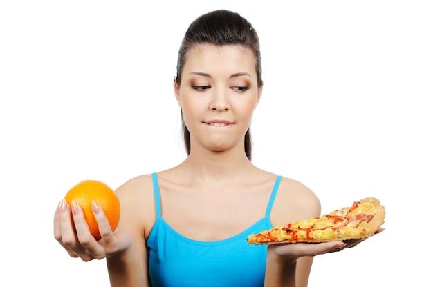 Junge frau wählen zwischen pizza und orange - nahaufnahme