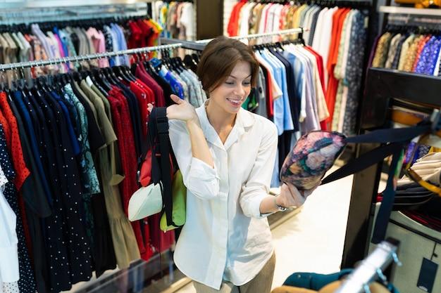 Junge frau wählt gürteltaschen im shop und sie schaut über einer mit blumendruck