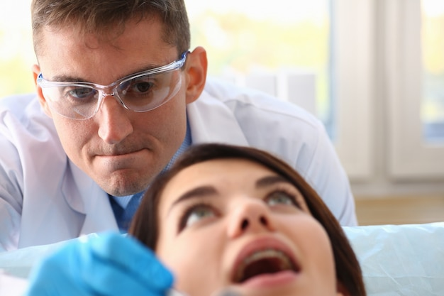 Junge frau während des termins mit zahnarzt in der klinik