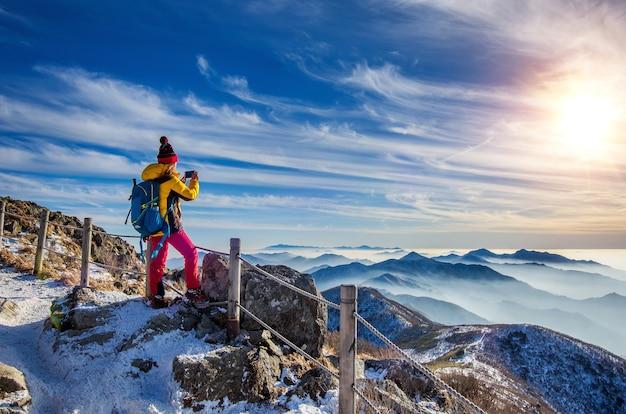 Junge frau wanderer, die foto mit smartphone auf gebirgsspitze im winter nimmt