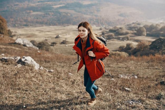 Junge frau wanderer, die in den bergen auf natur- und landschaftsrucksackjacke jeansstiefel reist. hochwertiges foto