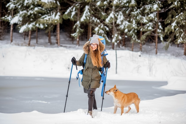 Junge frau wandert mit hund in der nähe des zugefrorenen sees und des verschneiten waldes