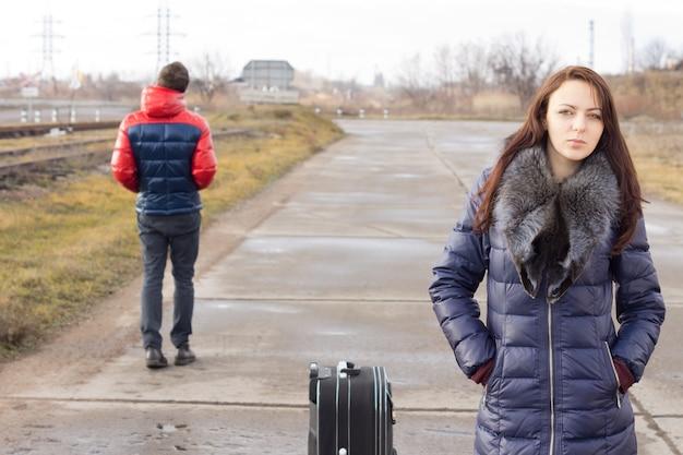 Junge frau wartet mit ihrem koffer mitten auf der straße auf einen aufzug, während ein junger mann in die entgegengesetzte richtung vorbeigeht