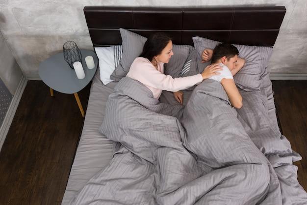 Junge frau weckt ihren beleidigten ehemann auf, während sie im bett liegt und pyjamas trägt, in der nähe des nachttisches mit kerzen im schlafzimmer im loft-stil mit grauen farben