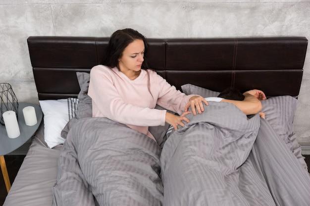 Junge frau weckt ihren beleidigten ehemann, der sich mit einer decke bedeckte, während er im bett lag und einen pyjama trug, in der nähe des nachttisches mit kerzen