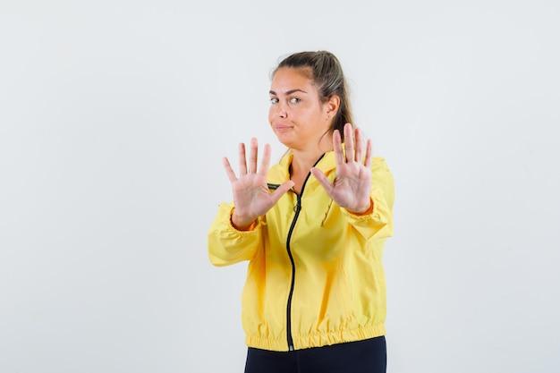 Junge frau weigert sich von etwas im gelben regenmantel und sieht widerstrebend aus