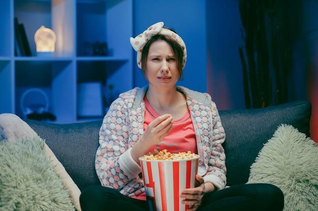 Junge frau weinen, während sie nachts einen sehr bewegenden film mit popcorn sieht