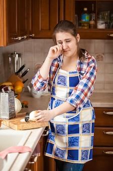 Junge frau weint in der küche beim zwiebelschneiden