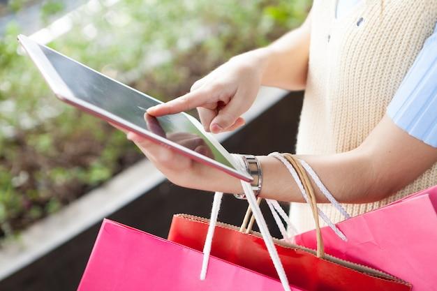 Junge frau, welche die digitale tablette online shoopping mit vielen farbtaschen verwendet