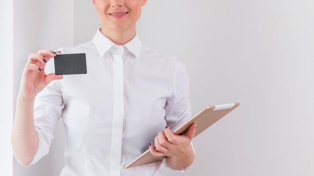 Junge frau, welche die digitale tablette zeigt graue visitenkarte anhält