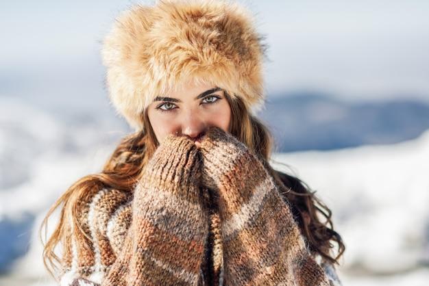 Junge frau, welche die schneebedeckten berge im winter genießt