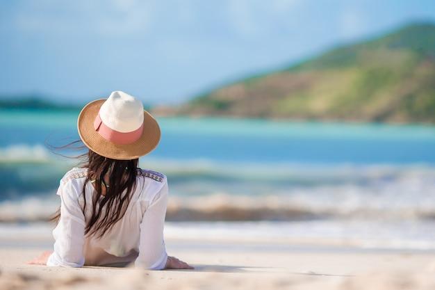 Junge frau, welche die sonne ein sonnenbad nimmt durch perfekten türkisozean genießt