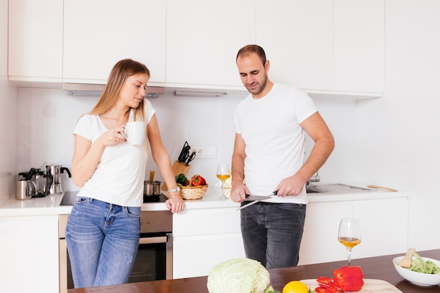 Junge frau, welche in der hand die kaffeetasse betrachtet ihren ehemann betrachtet das messer schärft hält