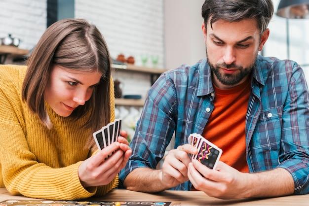 Junge frau, welche zu hause die karten spielt